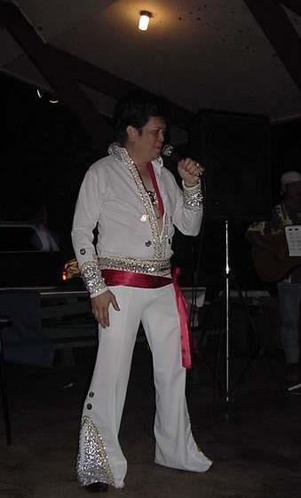 Buddy Reyes dressed as Elvis performing at an event.